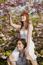 Woman plucking flowers while sitting on man s shoulders happy young women from cherry tree Royalty Free Stock Photography