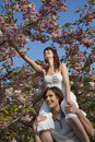 Woman plucking flowers while sitting on man s shoulders happy young women from cherry tree Stock Images