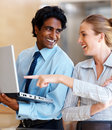 Woman pointing at the laptop held by a colleague Stock Photos