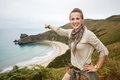 Woman pointing on something in front of ocean view landscape Royalty Free Stock Photo