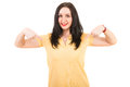 Woman pointing to blank t shirt happy her yellow tshirt isolated on white background Royalty Free Stock Photos
