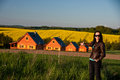 Woman pointing to row of homes standing in a field towards a with chimneys and behind them a field oil seed rape Stock Photos
