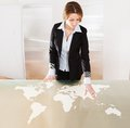 Woman pointing on transparent screen showing world map Stock Photo