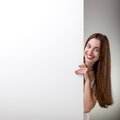 Woman pointing on white billboard over grey smiling empty background in studio Royalty Free Stock Image
