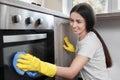 Woman polishing oven
