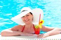 Woman in the pool with a cocktail in a hat white Stock Photos