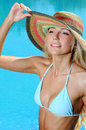 Woman in poolside attractive young bikini smiling on camera and touching her hat while sitting on the Royalty Free Stock Photos
