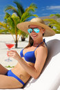 Woman at poolside with cosmopolitan cocktail in hat relaxing the Royalty Free Stock Photos