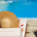 Woman at poolside with cosmopolitan cocktail in hat relaxing the Stock Photo