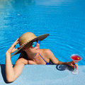 Woman at poolside with cosmopolitan cocktail in hat relaxing the pool Stock Photos