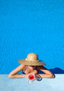 Woman at poolside with cosmopolitan cocktail in hat relaxing the pool Stock Images
