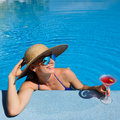 Woman at poolside with cosmopolitan cocktail in hat relaxing the pool Royalty Free Stock Image