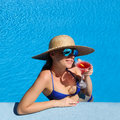 Woman at poolside with cosmopolitan cocktail in hat relaxing the pool Royalty Free Stock Photos
