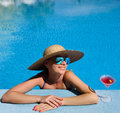 Woman at poolside with cosmopolitan cocktail in hat relaxing the pool Royalty Free Stock Images