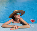 Woman at poolside with cosmopolitan cocktail in hat relaxing the pool Stock Photography