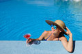 Woman at poolside with cosmopolitan cocktail in hat relaxing the pool Stock Image