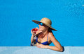 Woman at poolside with cosmopolitan cocktail in hat relaxing the pool Stock Photo