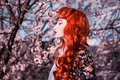 Woman portrait in spring flower garden. Valentine day background. Attractive redhead lady in dress. Woman in ribbon on nature Royalty Free Stock Photo