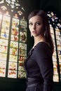Woman portrait stained glass window background beauty brunette in black dress over Stock Photos