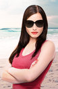 Woman posing on the beach beautiful a wearing sunglasses with her arms crossed Stock Photography