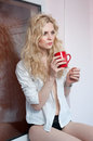 Woman posing with a big red cup of tea in her hands portrait young blond holding mug both wearing white shirt and black pants an Royalty Free Stock Photos