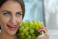 Woman posing with a bunch of grapes and smiling. Royalty Free Stock Photo