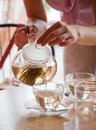 Woman is pouring green tea in cups Stock Photo