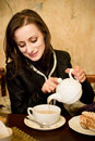 Woman pouring a tea in the cuptea Stock Photo