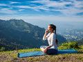 Woman practices pranayama in lotus pose outdoors Royalty Free Stock Photo