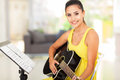 Woman practicing guitar cute young at home Royalty Free Stock Photography