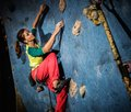Woman practicing rock climbing on a rock wall young indoors Stock Image