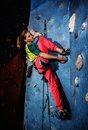 Woman practicing rock climbing on a rock wall young indoors Royalty Free Stock Photo