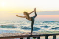 Woman practicing Warrior yoga pose outdoors over sunset sky background Royalty Free Stock Photo