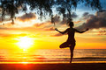 Woman practicing yoga on the beach during a beautiful sunset silhouette of Royalty Free Stock Image