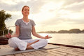 Woman practicing yoga on dock by river Royalty Free Stock Photo