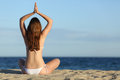 Woman practicing yoga exercises on the beach in summer with horizon over sea background Stock Images