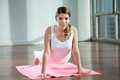 Woman practicing yoga on mat portrait of a beautiful young at gym Royalty Free Stock Photo