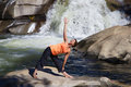 Woman practicing yoga a near a waterfall Royalty Free Stock Image
