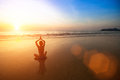 Woman practicing yoga on sea beach during wonderful sunset. Royalty Free Stock Photo