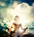 Woman Practicing Yoga by the Sea. Bokeh Background Royalty Free Stock Photo