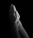 Woman praying on black background s hands held up in prayer Stock Image