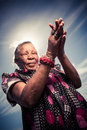 Woman praying old african homeless deep in prayer with the sky as a background Stock Images