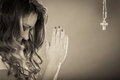 Woman praying to god jesus with cross necklace. Royalty Free Stock Photo