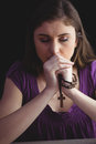 Woman praying with wooden rosary beads Royalty Free Stock Photo