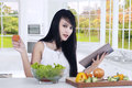 Woman prepares salad while reading book Royalty Free Stock Photo