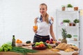 Woman preparing dinner in a kitchen, drinking juice concept cooking, culinary, healthy lifestyle. Royalty Free Stock Photo