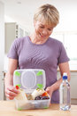 Woman Preparing Healthy Lunchbox In Kitchen Royalty Free Stock Photo