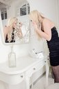 Woman preparing for a night out standing applying her makeup in large mirror over white vanity Stock Image