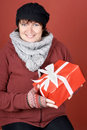 Woman with present happily smiling a christmas over red background Stock Images