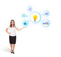 Woman presenting light bulb with colorful graphs Royalty Free Stock Photo
